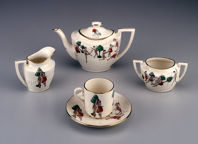 tea set made of creamy colored pottery then glazed; now has crazing; decorated with all wooden Dutch dolls known as Peg Woodens, Penny Woodens or Nurnberg Fille, which had black painted hair and orange or deep pink painted slippers; other colors include brown, red and green; set came in the original box