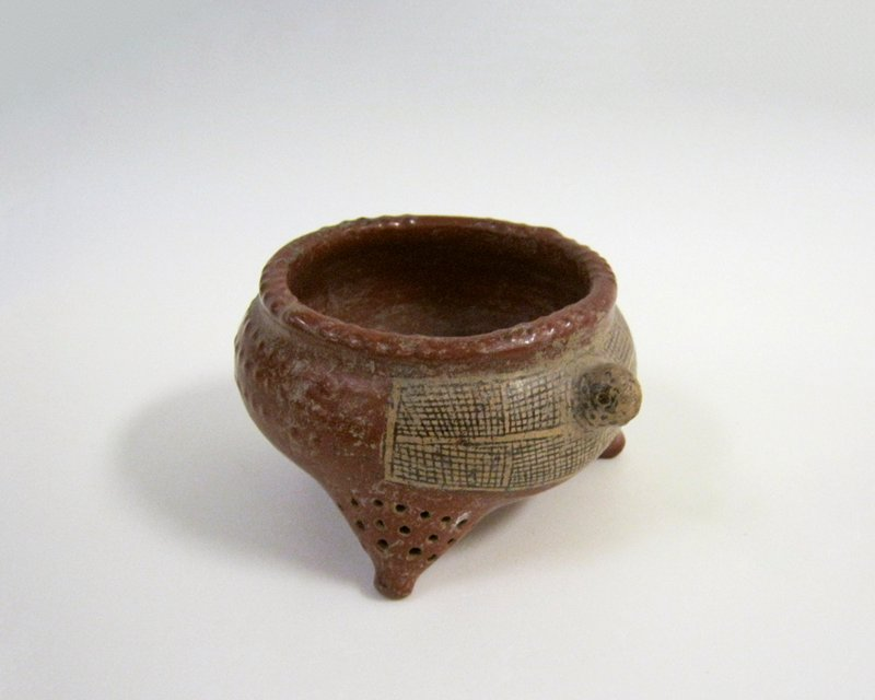 three legged round bowl; small holes on each leg; dark red pigment; turtle head protruding on one side; rectangular section on off-white and black hatched decoration around turtle head raised bumps scattered on sides; unglazed