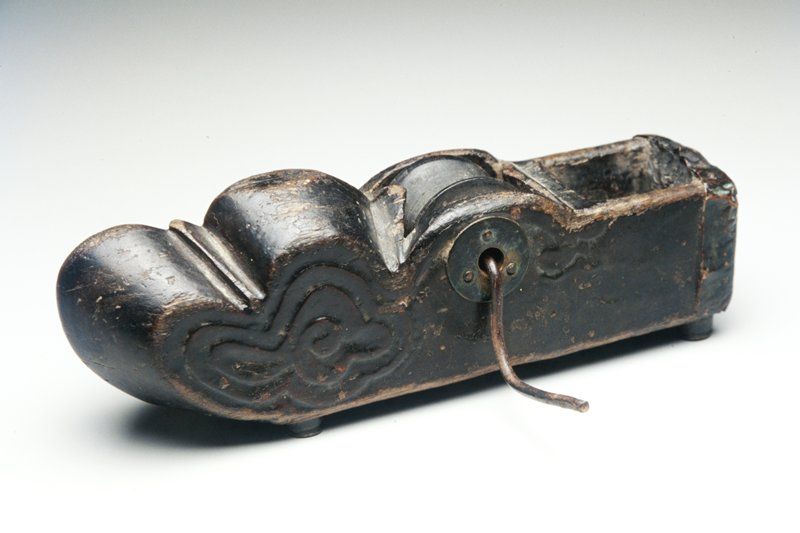 ink well and hand operated wheel with string wrapped around wheel and lead through inkwell; set in wood block carved with clouds at one end; four brass feet and side discs