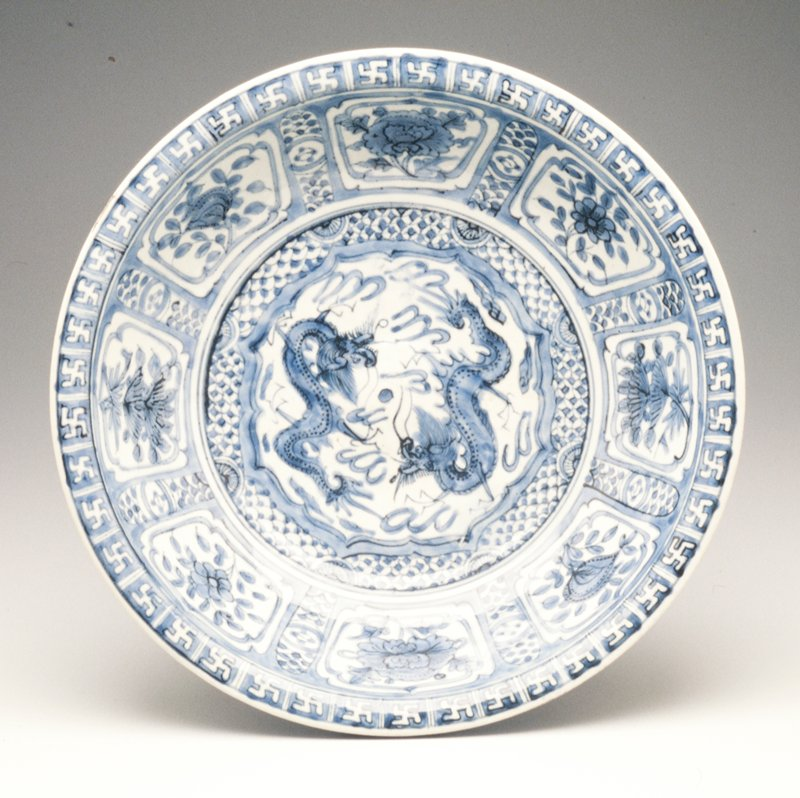 blue and white, painted at center with two dragons confronted around a pearl amongst fire-scrolls within an octafoil panel reserved on a scale-pattern ground, below eight floral lappet shaped panels on the sides