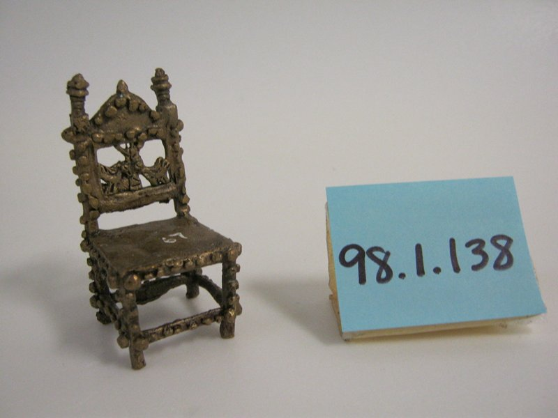 Chair with back, no arms; decorated with applied spheres; back decorated with two animals and a tree
