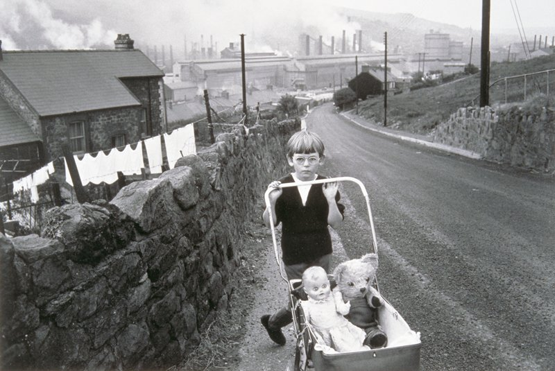 small boy pushing doll carriage with doll and bear inside; stone wall to his PR; white wash on line behind wall; large industrial scene in far background.