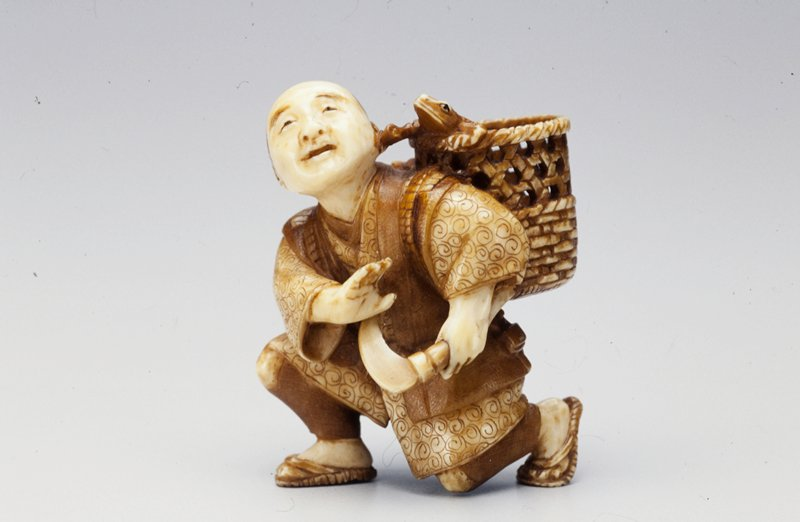 man kneeling on proper left knee is startled as the frog in the basket over his shoulder touches his face with its front flipper; man carries axe in proper left hand