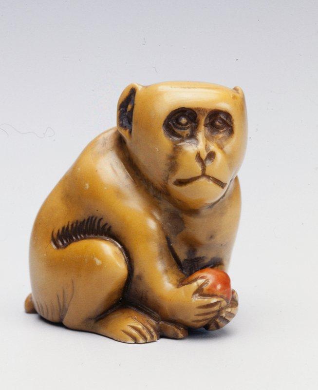 crouching monkey holding a peach