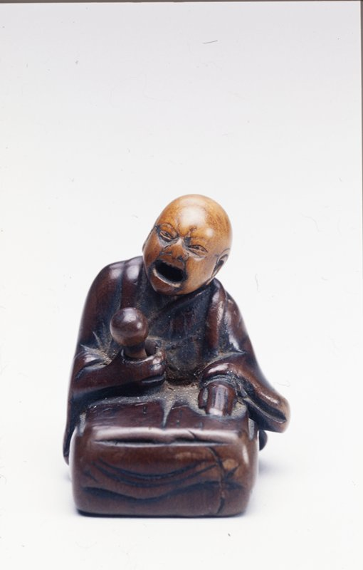 seated priest-chanter with open mouth and movable head; proper left hand rests on a book on a cushion, proper right hand holds a movable wand