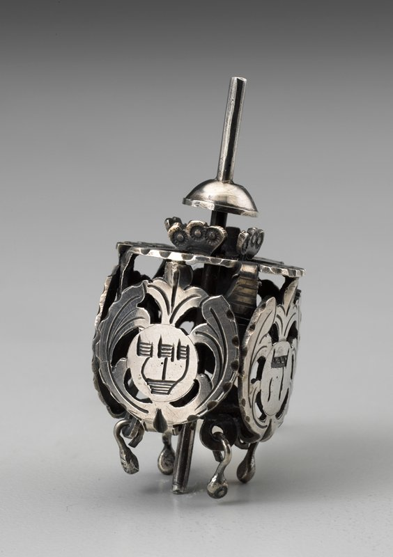 six-sided metal dreidel with openwork sides, with Hebrew letters on four sides; square wood base