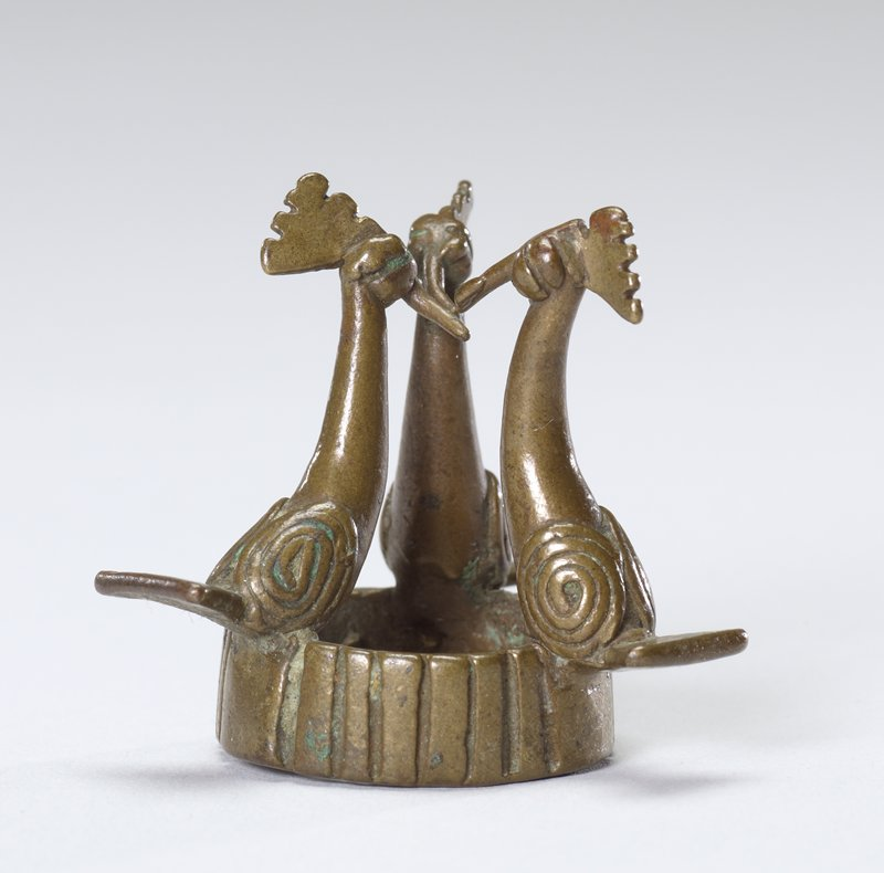 Three birds sitting on top of a ring; ring has incised vertical lines all the way around; each bird has spiral on one side of body