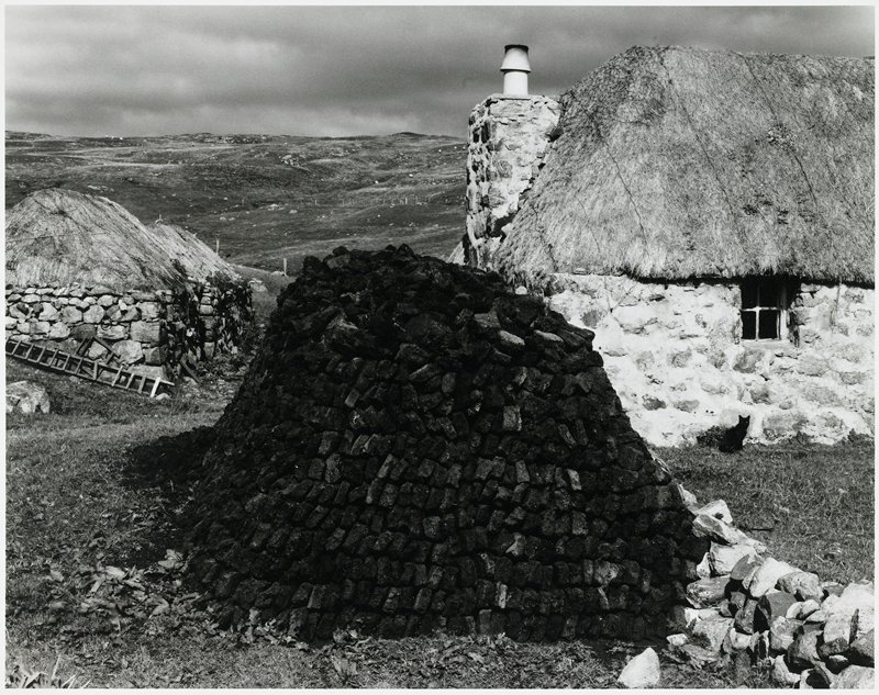 peat pile with buildings in background