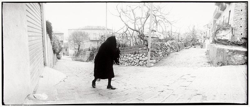 old woman walking on a brick road, black shawl and coat, huddled