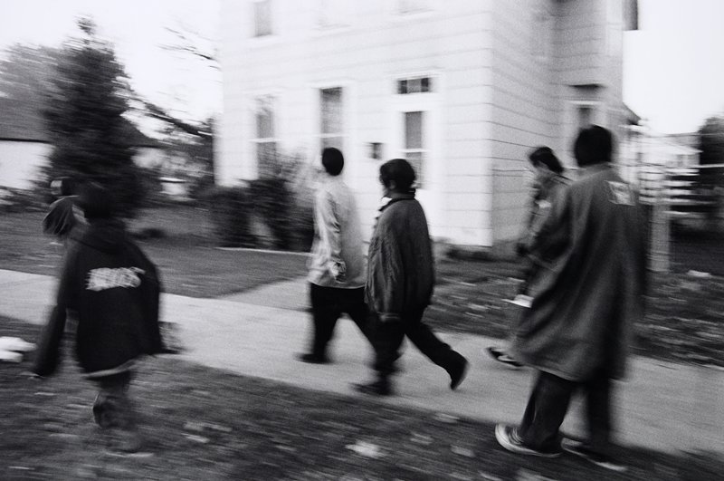 black and white photo; blurred image of six people walking in front of house