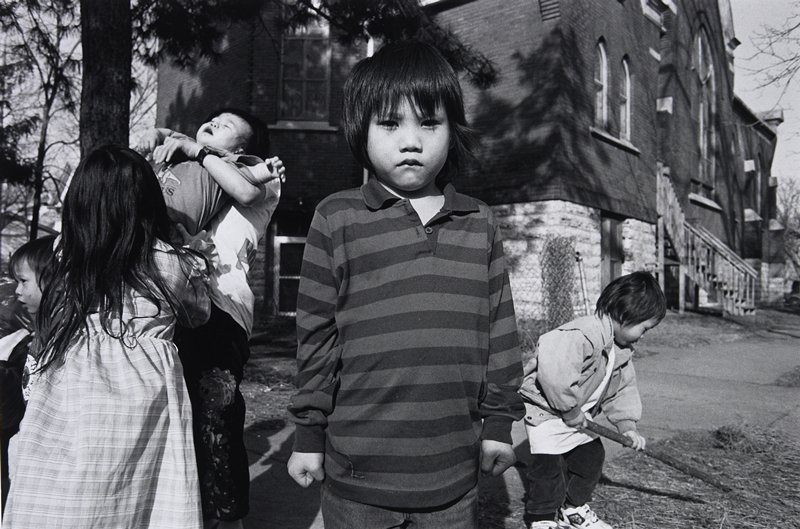 black and white photo of boy center, group on left, little boy with stick on right