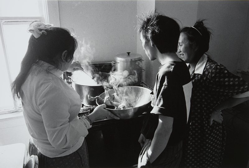 black and white photo of two women and man standing at stove