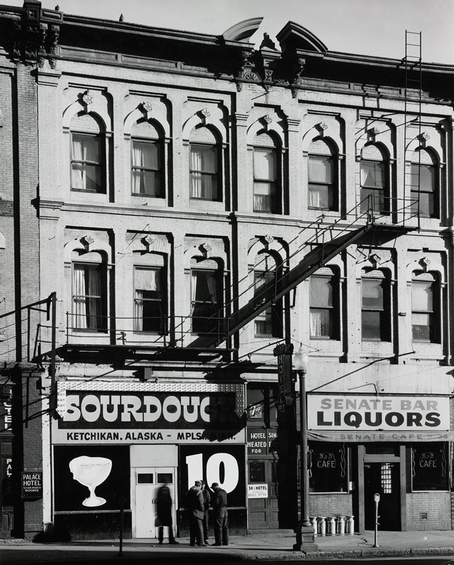 four men standing on the sidewalk in front of a bar with a large 'SOURDOUGH' sign; another bar to right; windows above storefronts