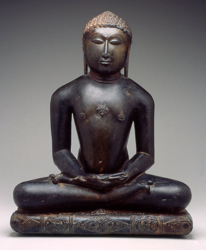 figure seated in dhyanasana with hands in lap; cushion below figure carved with foliate sprays and central quatrefoil medallion; crest ornamented with a diamond-shaped srivatsa; back uncarved