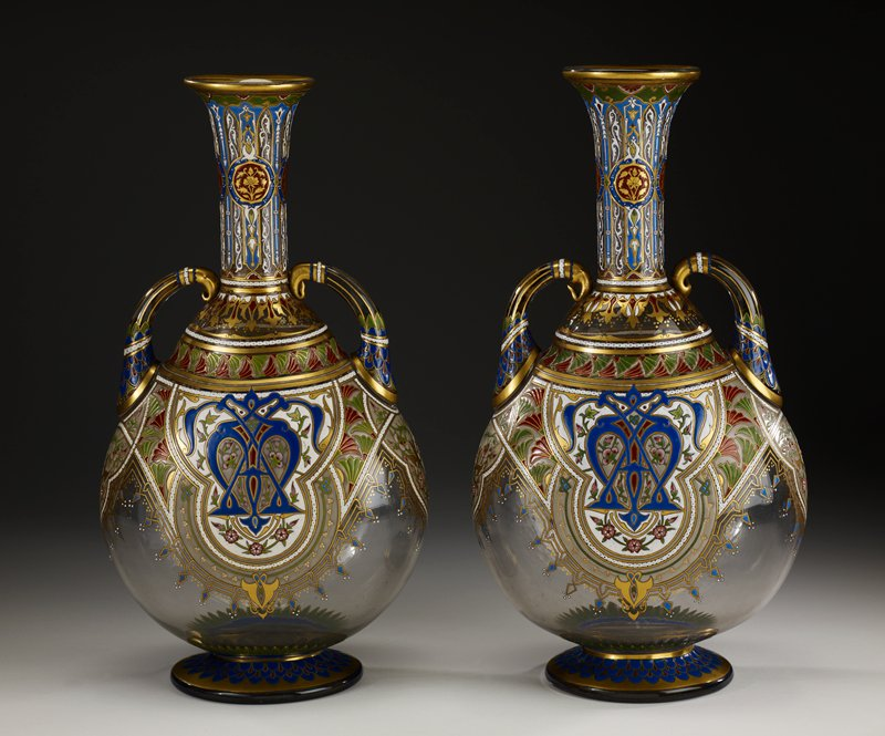 tall neck with flared rim; short handles at shoulders; red, blue, green, white and gilt decoration of stylized foliage and geometric patterns; spreading foot with blue, red and gilt 'scales'