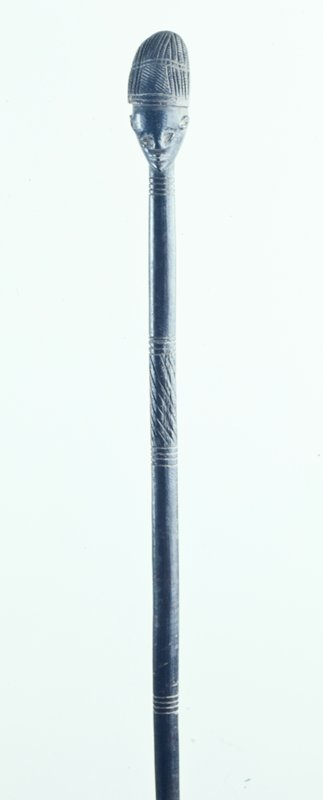 Staff with head on top; head has very high ears, uneven eyes, hairstyle sticking up in front with a bald, pointed back of head; staff decorated with incised rings and diagonal lines