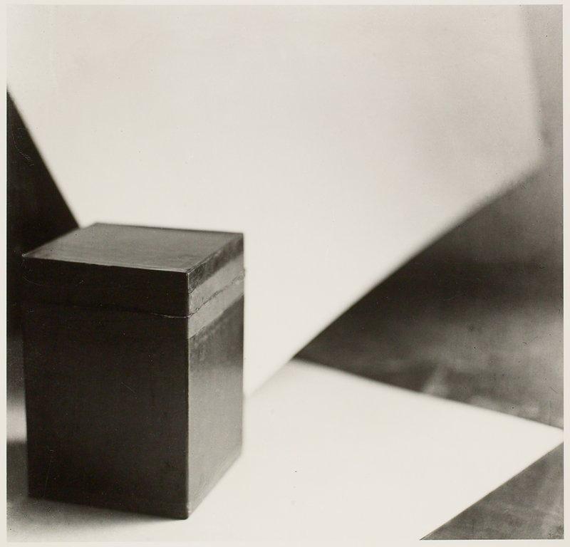 black lidded box lower left quadrant, sitting on white surface