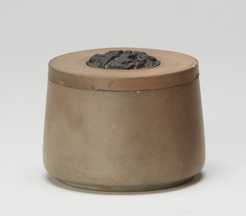Yixing ware; grey container with heavy base; grey lid with removable central black plaque carved with boy pulling on an oxen's reigns with trees in background