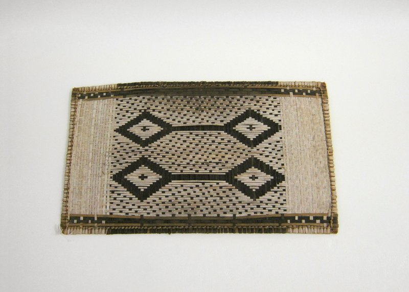 Small mat with geometric design in center flanked by 2 bands of light fibers; design consists of 2 pairs of diamonds with central crosses connected by bars in dark fibers