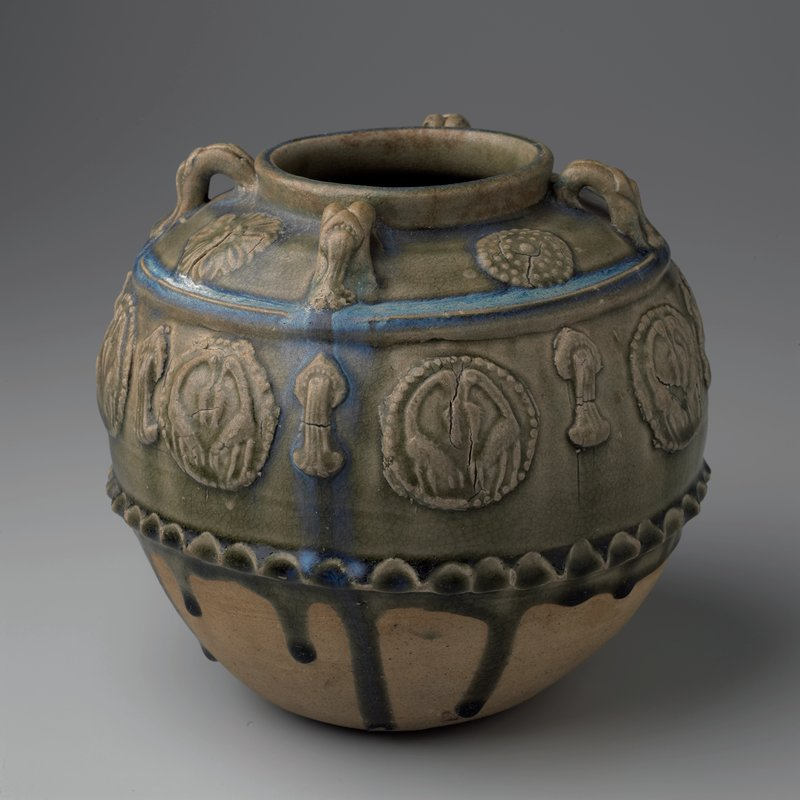 spherical jar with 4 small double strand lug handles below mouth; crinilated rib around center of body; 4 floral medallions between handles; 8 medallions with pairs of cranes holding fish alternating tassels and lotus pods on body; green glaze pooling to bright blue; bottom 1/3 unglazed