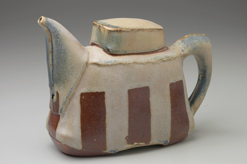 constructed flattened wedge form; 3 wax resist rectangles on each side, one below spout; bluish-grey glaze; fat spout with narrow opening; thick lid