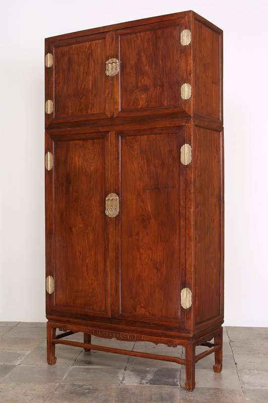 top double-doored cabinet with 2 interior shelves, pin closure and 3 hanging pendant pulls rests on large cabinet; double-doored cabinet with 3 shelves, 2 drawers, pin closure and hanging pendant pulls rests on a stand with carved apron