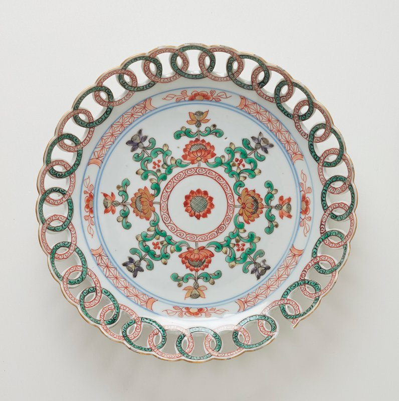 PIECE BROKEN ON TOP OF DISH; plate, green and red floral design with open work border of circles
