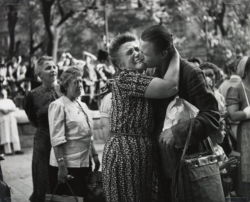 man with slicked-back hair carrying a paper sack in his PL hand and a bag over the same arm kissing a crying woman wearing a flowered dress; other people in background
