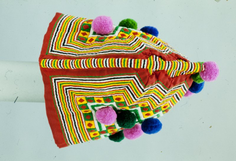 Rooster hat, cotton, fold and tuck construction techniques, 17 pompoms attached. Coarse cotton used may indicate hat was made in Laos. Worn by a child.