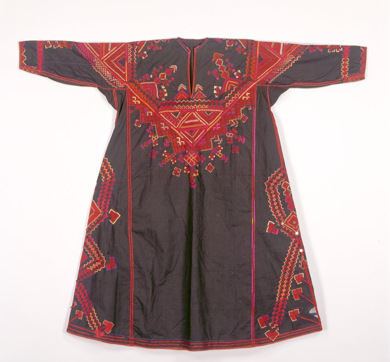 black ground with embroidery in reds (primarily) and other colors, especially at neck, arms and sides