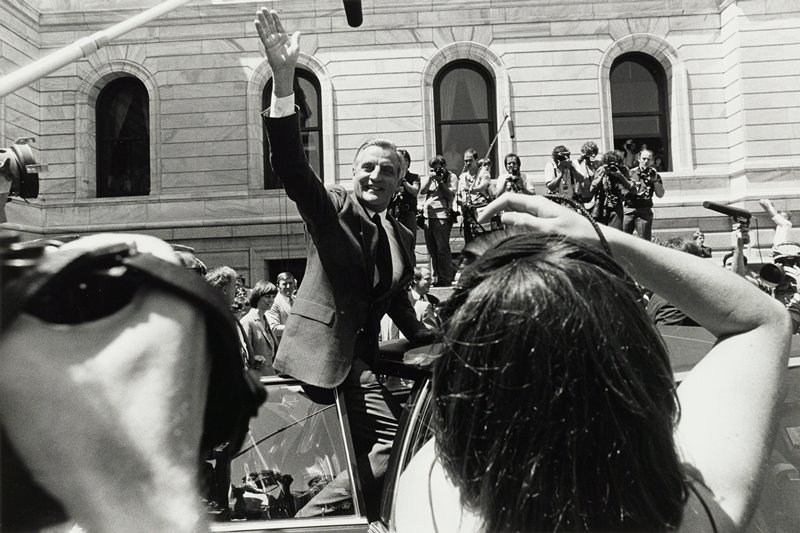 Walter Mondale waving to crowd from convertible with photographers background right