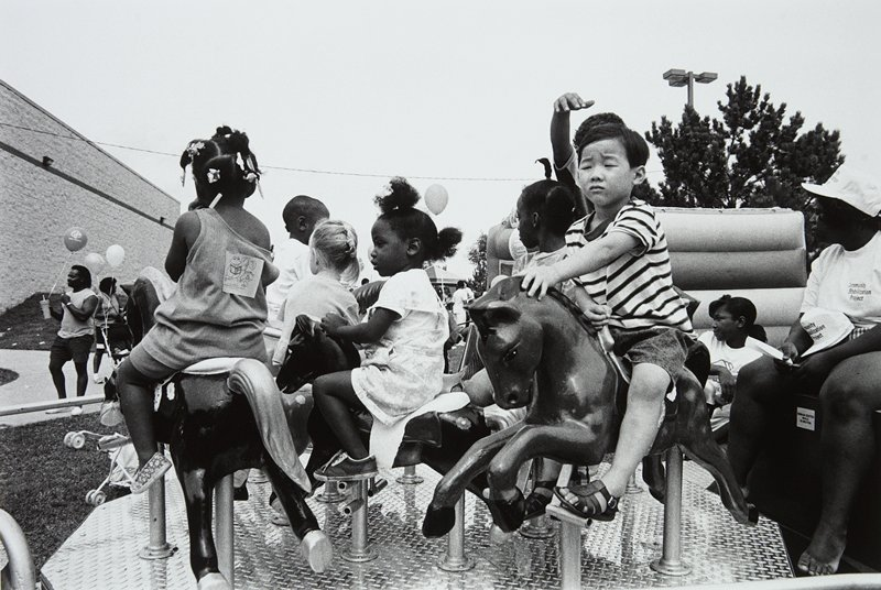 black and white photo of children on horses in merry-go-round