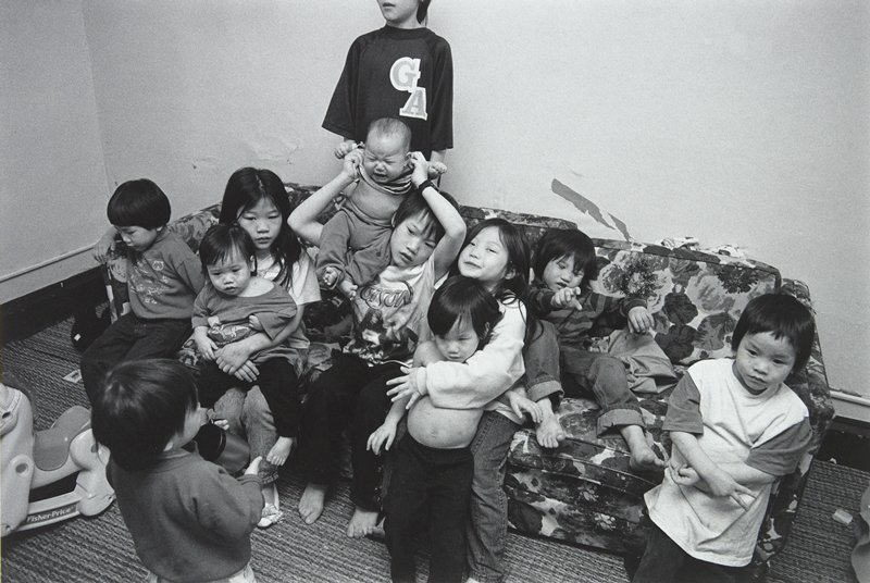 black and white photo of eleven children on couch