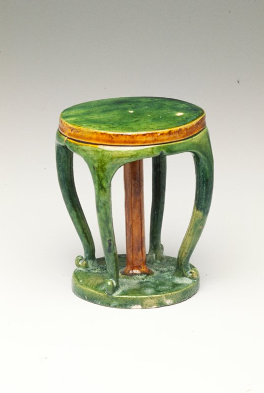 Tomb furniture; round table with short apron and four curving decorative legs and center support resting on a small base; edge of tabletop and center support glazed tan, all other parts glazed green