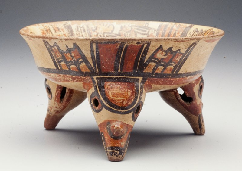Bowl with three legs shaped like bird's heads; tan glaze with designs in brown and red; reclining figures alternating with horizontal stripes along interior rim; legs are hollow with a ball inside each one and three holes (eyes and on mouth)