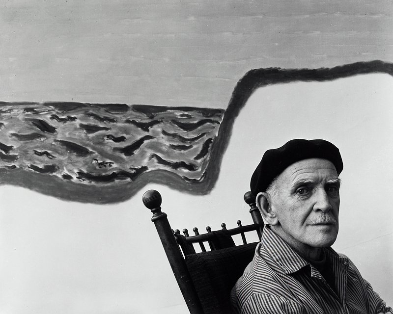 man wearing striped shirt and beret seated in LRQ; painting on wall behind him
