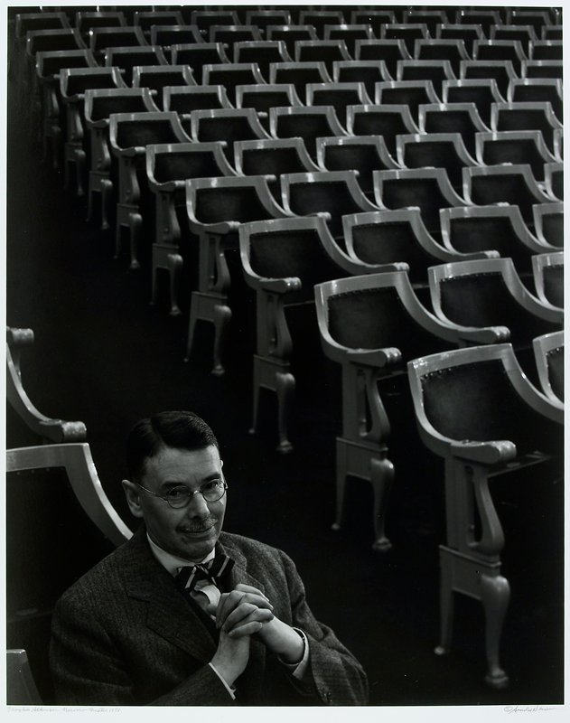 man seated, hands together, in LLC; theater seats fill rest of image