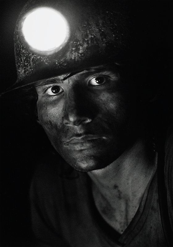 portrait of young miner with lit helmet; face is dirty