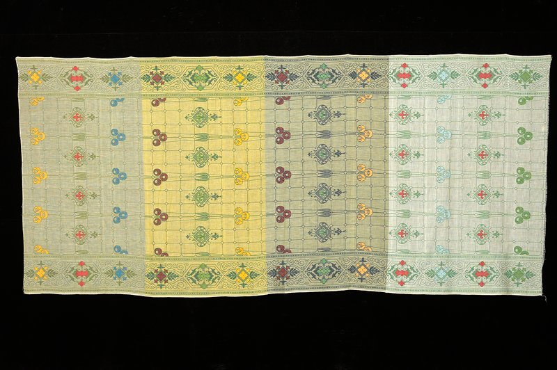 4 colors ground (from top) cream, yellow, cream, white; scrolling foliate borders on long sides with central gridded section with fleur-de-lis in diamonds and abstracted tulips; woven in greens, blues, reds and yellows. Woven fabric