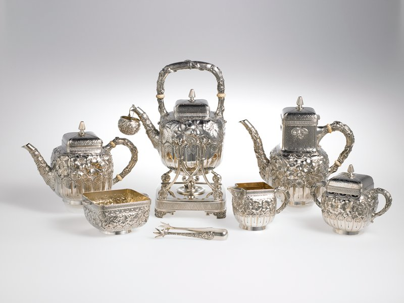 eight piece tea and coffee service, 1883; Aesthetic Style; design of embossed cherry blosssoms on matted ground, with lobing and fans at the base and demi-roundels above; each superstructure decorated with alternating hammered and basket weave bands; handles and spouts formed as bamboo sprigs with entwining vines