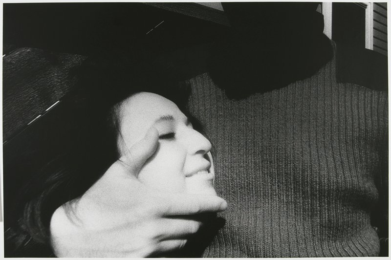 head of a smiling woman with dark hair pressed against the chest of a man wearing a sweater, his face out of the picture, his PR hand cradling the woman's chin