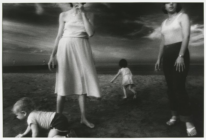 2 standing women woman at L wearing dress, barefoot, with head outside picture; woman at R wearing thongs, jeans and a tank top, holding a cigarette; girl running in background behind women; boy crawling at L in foreground; on a beach; matted