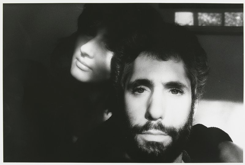 close-up of a bearded man with dark wavy hair; woman's face visible behind man on L, with eyes in shadow; 3 windows in URC; matted