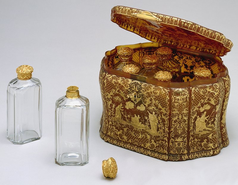group includes oblong casket in slightly bombé shape with shaped corners and a key; contains 8 glass bottles with gold lids; decoration on box shows scenes from legends of the miracles of St, Nicolas of Myra