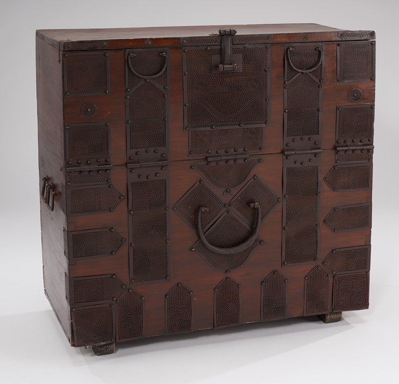 chest with hinge on front; door on front swings downward to open; pairs of metal handles at sides and on door; large decorative handle on bottom panel on front; applied metal sheets with geometric openwork designs on front; large lock included