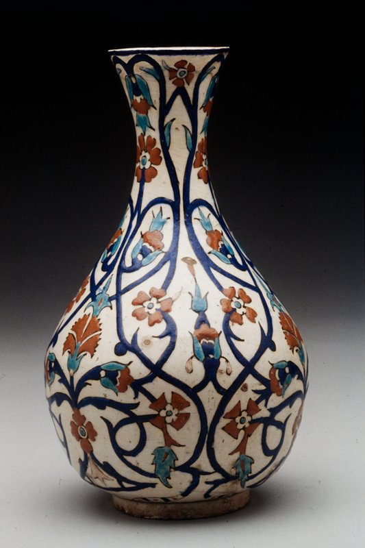 Vase with low base-rim, wide rounded body and tall,thin, flaring neck. It is covered with white opaque glaze and decorated with symetrical floral pattern with deep blue curving stems, turquoise tiny leaves and tomato red pinks, 5 petaled round flowers and conventionalized floral forms.