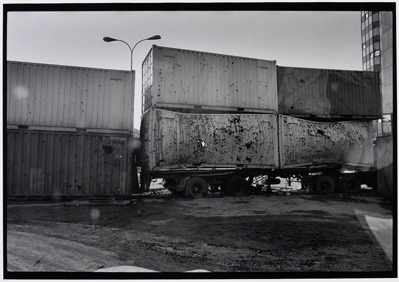 stacked truck trailers filled with bullet holes