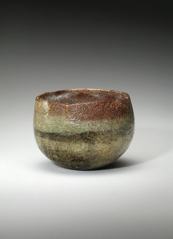 very rounded bowl with various earth toned clays in a gradient, including green and rust colors