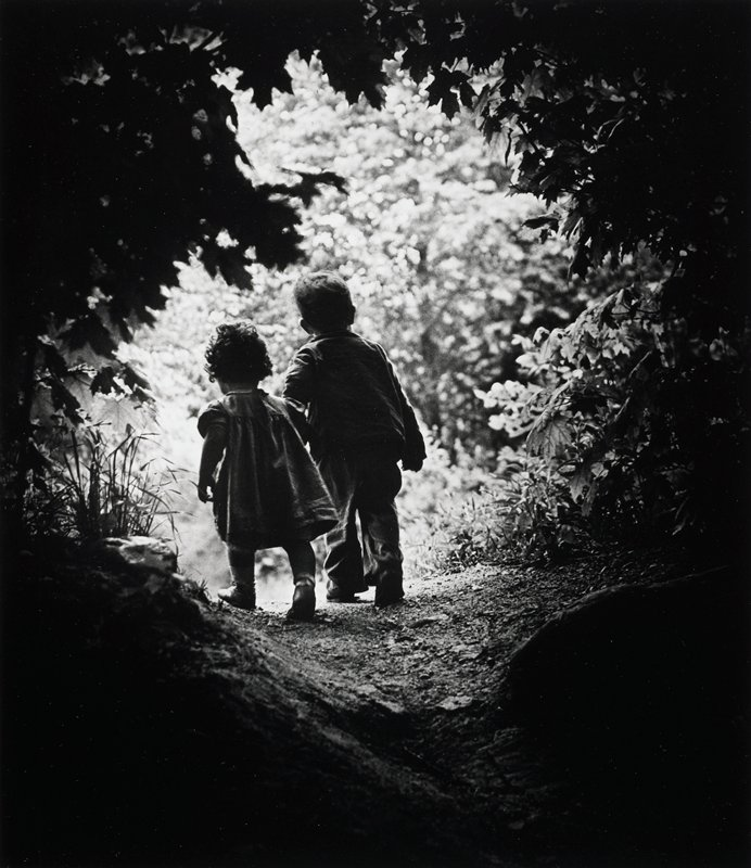 two small children walking hand in hand along a path in a wooded garden