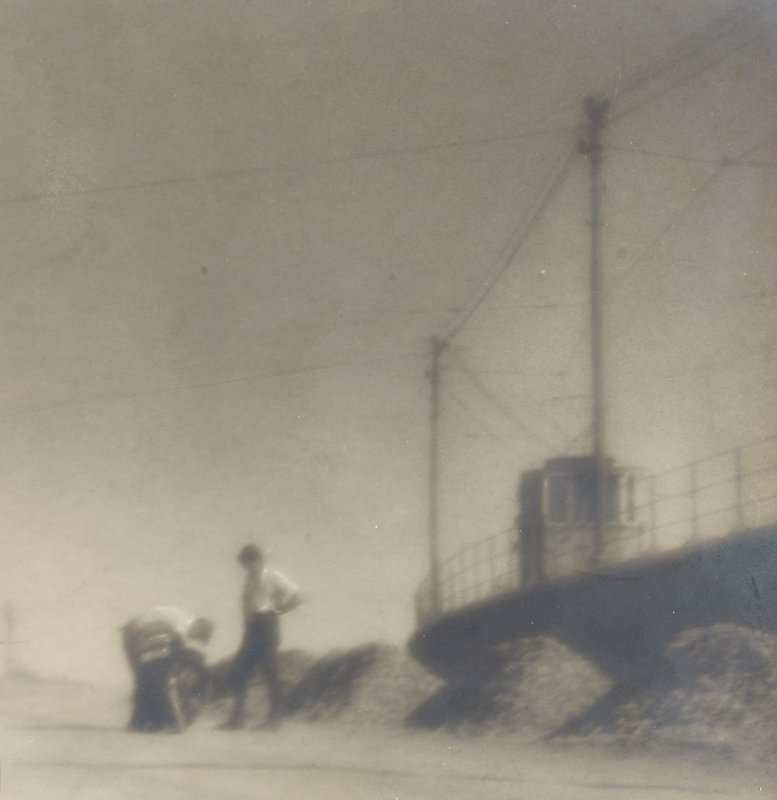 hazy image of two men standing next to a large boat